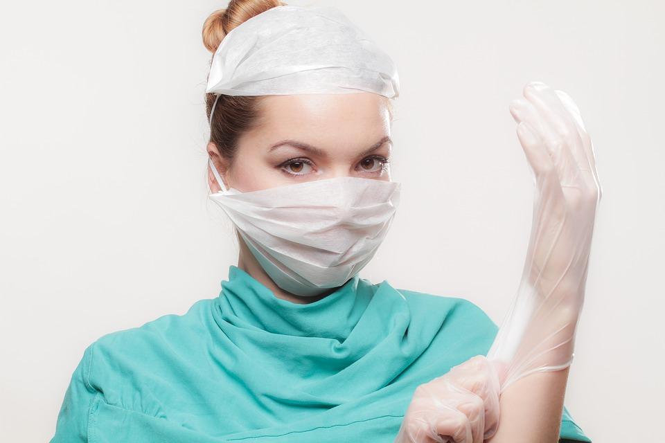 Foto af kvindelig operationslæge, der tager handske på